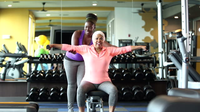 senior african-american woman at gym, personal trainer - dumbbell stock videos & royalty-free footage