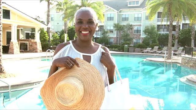 senior afroamerikanerin am resort-pool - aktiver senior stock-videos und b-roll-filmmaterial