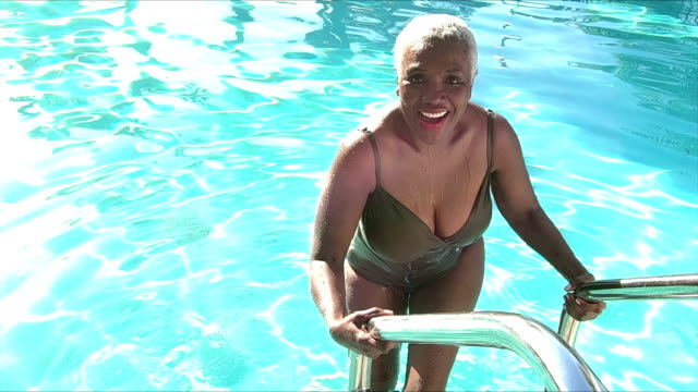 senior african-american woman climbing out swimming pool - ladder stock videos and b-roll footage