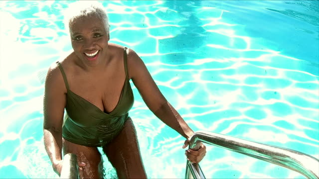 Senior African-American woman climbing out swimming pool