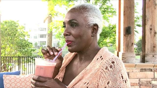senior african-american woman enjoying smoothie - smoothie stock videos & royalty-free footage