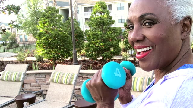 senior african-american woman exercising, handweights - fitness tracker stock videos and b-roll footage