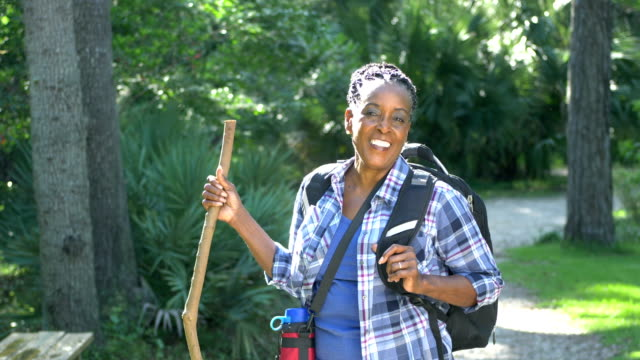 senior african-american woman hiking in the woods - plaid shirt stock videos & royalty-free footage