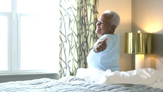 vidéos et rushes de femme afro-américaine principale dans le lit, se réveillant - brightly lit