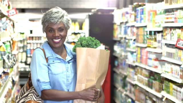 hochrangige afroamerikanerin in supermarkt-gang - papiertüte stock-videos und b-roll-filmmaterial