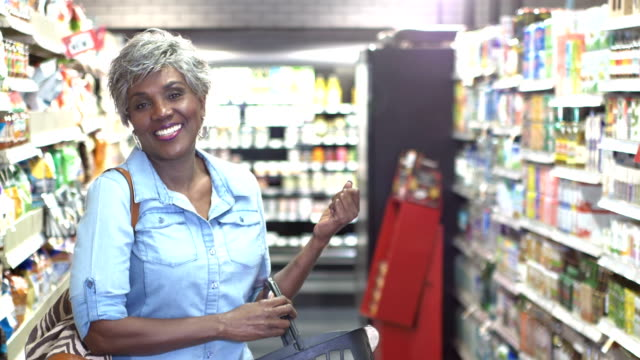 senior african-american woman in supermarket aisle - shopping basket stock videos and b-roll footage
