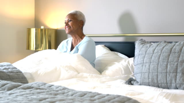 senior african-american woman lying in bed, gets up - lying on side stock videos & royalty-free footage