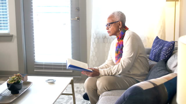senior african-american woman on couch reading book - reading glasses stock videos & royalty-free footage