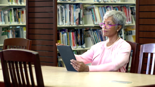 senior african-american woman reading in library - e book stock videos & royalty-free footage