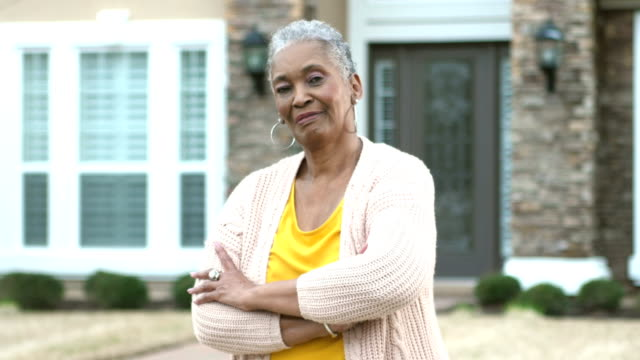 senior african-american woman standing in front of house - in front of stock videos & royalty-free footage