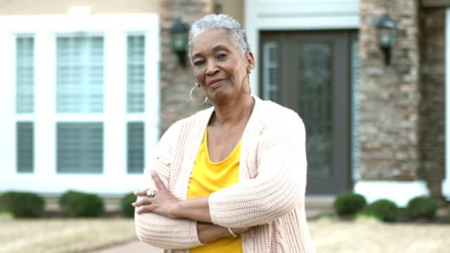 vidéos et rushes de femme afro-américaine aînée restant devant la maison - devant