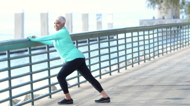 vídeos de stock e filmes b-roll de senior african-american woman stretching legs - esticar