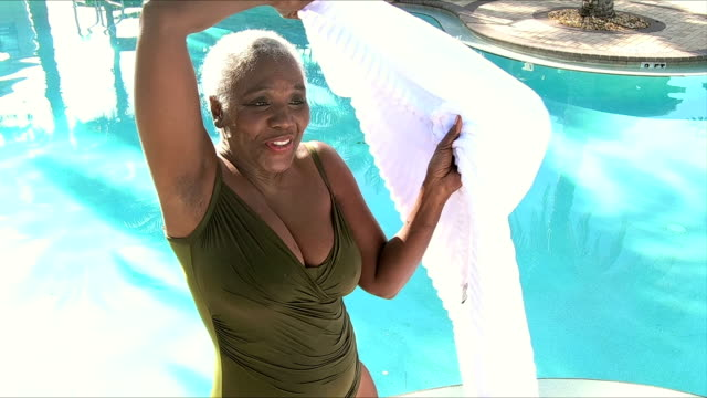 senior african-american woman wrapped in towel by pool - wrapped in a towel stock videos & royalty-free footage