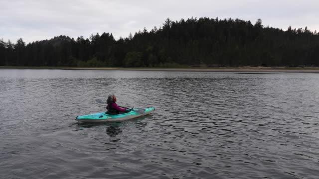 vídeos de stock e filmes b-roll de senior age woman kayaking - insulano do pacífico