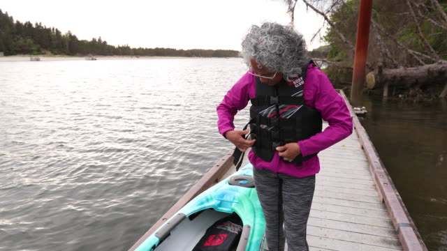 Senior age woman putting on lifejacket