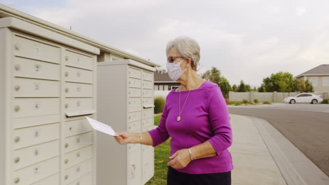 senior age woman voting by mail - letterbox stock videos & royalty-free footage