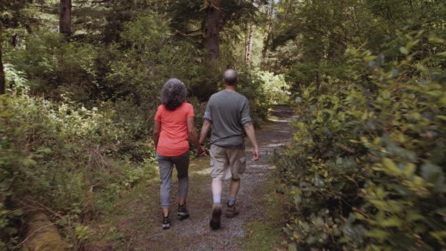Senior aged couple hiking through the woods