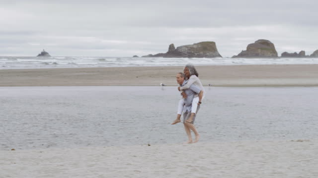 senior aged man giving his wife a piggy-back at the beach - pacific islander couple stock videos & royalty-free footage