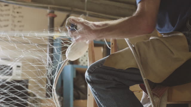 UHD 4K: Senior aged man tying fishing gill nets in a wharehouse