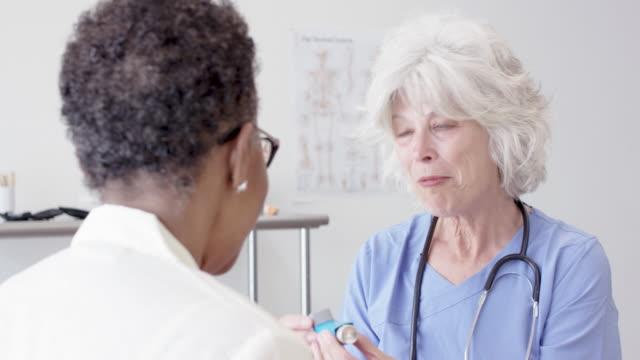 vídeos de stock e filmes b-roll de senior aged nurse helping her senior aged female patient - asmático