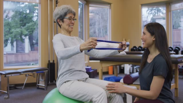 senior aged woman using a resistance band at a physical therapy session - physical therapist stock videos & royalty-free footage