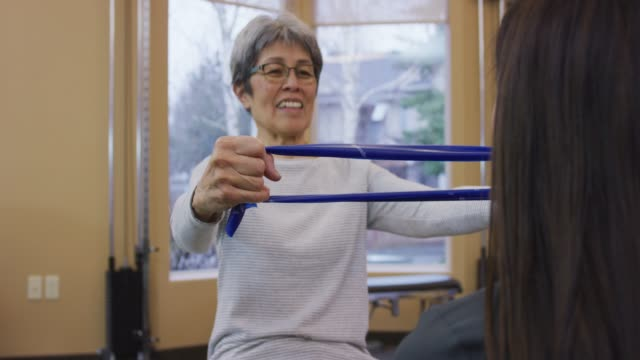 senior aged woman using a resistance band at a physical therapy session - rehabilitation center stock videos & royalty-free footage