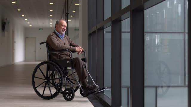 vídeos de stock e filmes b-roll de senior amputee patient on wheelchair looking through window daydreaming very cheerfully - cadeira de rodas