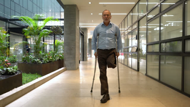 senior amputee patient using crutches walking through hospital's corridor - amputee stock videos & royalty-free footage