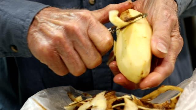 Senior en peeling färsk potatis med potatisskalare