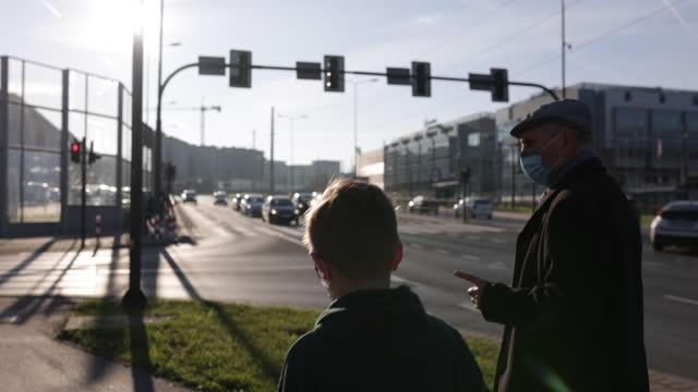 vidéos et rushes de senior et ses petits-fils marchant dans la zone urbaine pendant la pandémie de covid-19 - traverser
