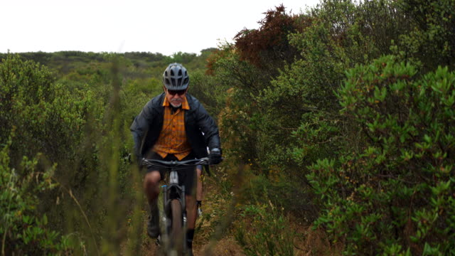 ms senior and mature friends riding mountain bikes on trail on lush hillside - bicycle trail outdoor sports stock videos & royalty-free footage