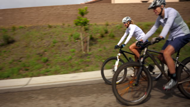vídeos de stock, filmes e b-roll de ts senior and mature friends riding mountain bikes through neighborhood after trail ride - estilo de vida ativo