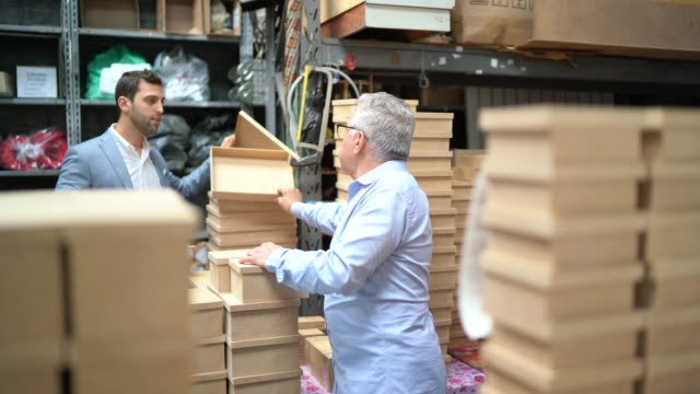 senior and young business owner checking products in a storage room, using digital tablet - small business stock videos & royalty-free footage