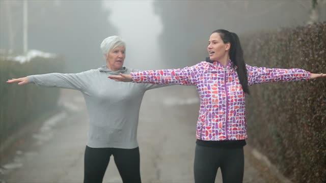vidéos et rushes de seniors et jeunes femmes se réchauffer en plein air - cheveux gris