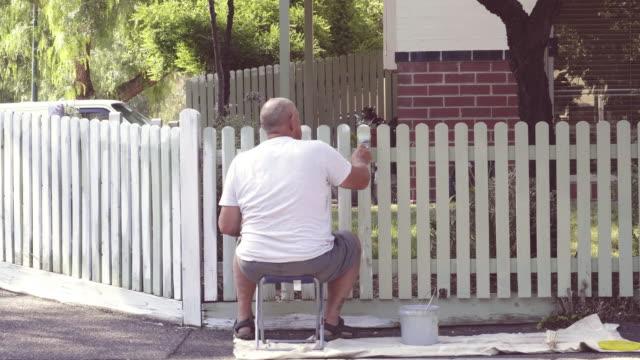 vidéos et rushes de senior applying paint to fence with care - clôture jardin