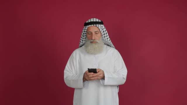 senior arabisk ringer upp ett meddelande på en smartphone på en röd bakgrund - 50 59 years bildbanksvideor och videomaterial från bakom kulisserna