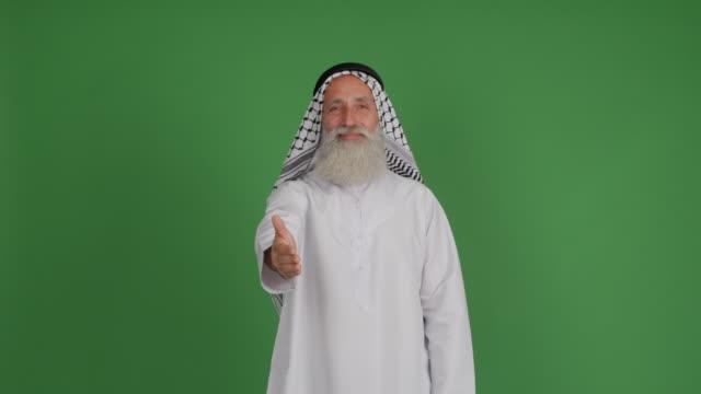 senior arabisk sträcker sig en hand och ler på en grön bakgrund - 50 59 years bildbanksvideor och videomaterial från bakom kulisserna