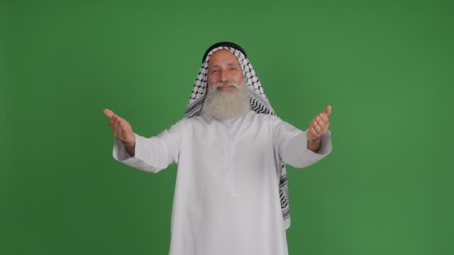 senior arabisk hälsar händer ute och ler på grön bakgrund - 50 59 years bildbanksvideor och videomaterial från bakom kulisserna