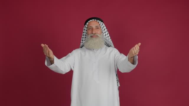senior arabisk hälsar händer ute och ler på röd bakgrund - 50 59 years bildbanksvideor och videomaterial från bakom kulisserna