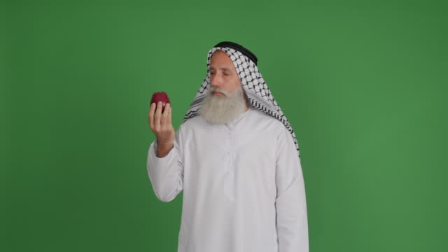 senior arabiska visar apple och tummen på grön bakgrund - 50 59 years bildbanksvideor och videomaterial från bakom kulisserna