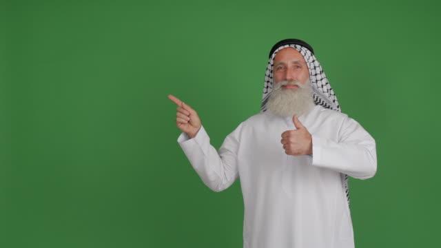 senior arabiska visar kopia utrymme och tummen upp på grön bakgrund - 50 59 years bildbanksvideor och videomaterial från bakom kulisserna