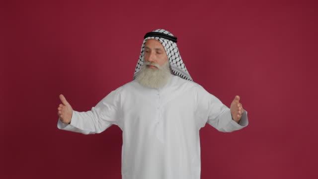 senior arabiska visar kopia utrymme och tummen upp på röd bakgrund - 50 59 years bildbanksvideor och videomaterial från bakom kulisserna