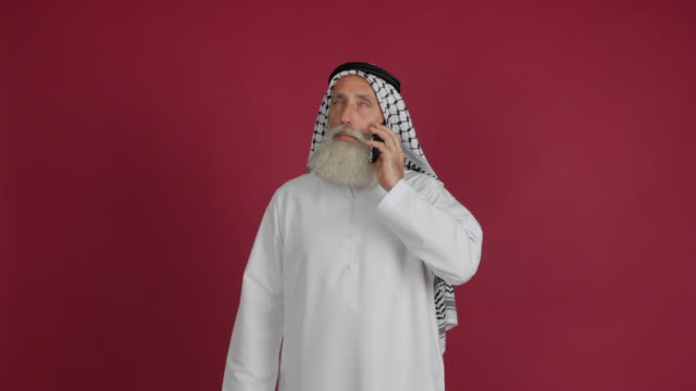 senior arabiska talar i telefon på en röd bakgrund - 50 59 years bildbanksvideor och videomaterial från bakom kulisserna