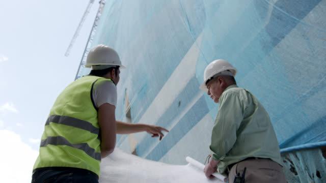 上を指差して話しながら青写真を見ているシニアアーキテクトとエンジニア - 土木技師点の映像素材/bロール