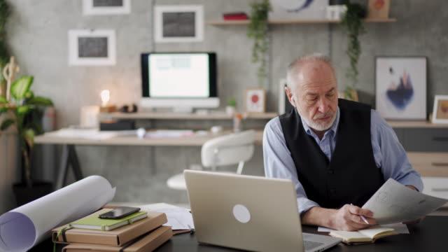 vidéos et rushes de architecte principal à son petit bureau à la maison - seniornaute
