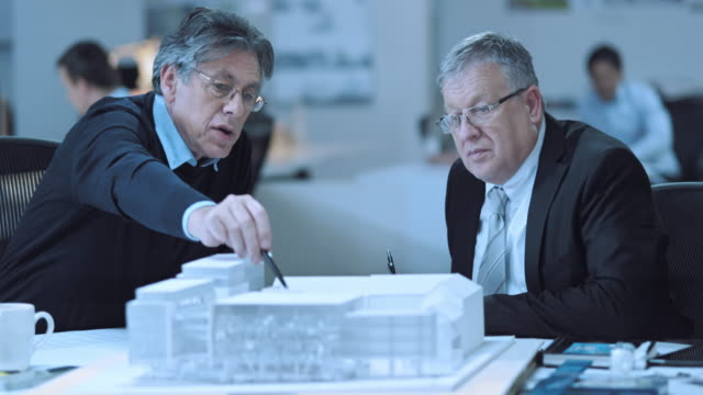 ds senior architect discussing details of model with investor - architect model stock videos and b-roll footage