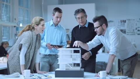 stockvideo's en b-roll-footage met ds senior architect toezicht op een jong team van architecten - brainstormen