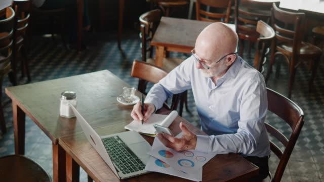 senior argentinischen geschäftsmann tun finanzen hinter dem laptop im restaurant - italienischer abstammung stock-videos und b-roll-filmmaterial