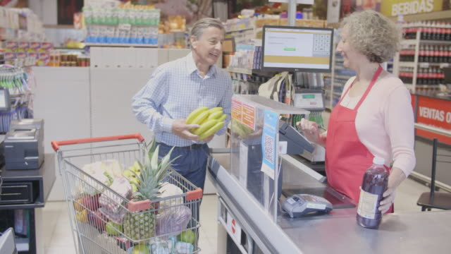 vídeos de stock e filmes b-roll de senior argentinian man checking out in supermarket - carrinho de compras