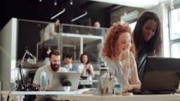 Senior art director mentoring new intern in modern office
